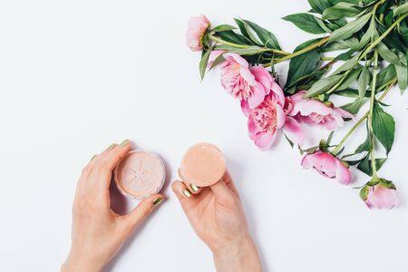 Vista superior de las manos de la mujer sosteniendo el aplicador de hojaldre de maquillaje con polvo facial beige suelto cerca de un ramo fresco de peonías rosas sobre fondo blanco, endecha plana. Foto de archivo