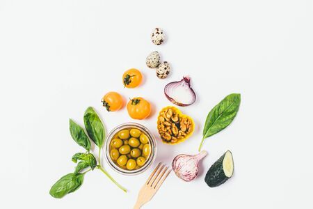 Healthy food flat layout of olives, walnuts, garlic, cucumbers, onions, quail eggs, yellow tomatoes and greens on white background.