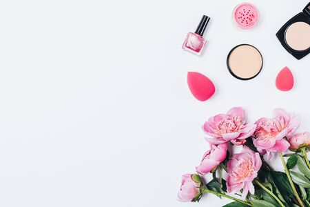 Flat lay composition bouquet of pink peony flowers, makeup products and tools on white background with copy space.
