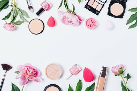 Floral makeup background of peonies next to cosmetic products and accessories on white table with an horizontal empty space in middle, flat lay.