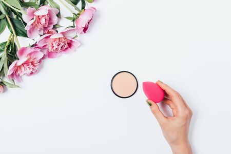 Top view woman's hand holding makeup blending sponge applicator with beige facial powder near beautiful bouquet of pink peonies on white background, flat lay.