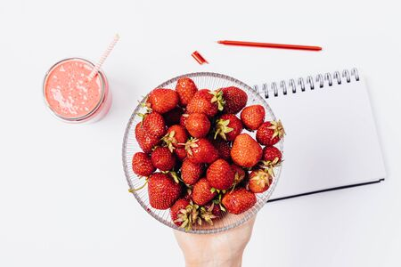 View from above females hand holding bowl of fresh strawberries over white table with empty notebook and smoothie.