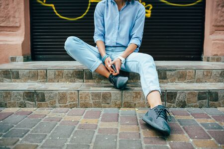 Unrecognizable young woman wearing blue shirt and jeans relaxing sitting steps on city street at summer day.