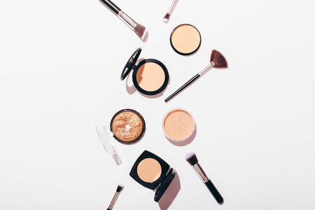 Stylish flat lay composition of makeup products and accessories on white background with bright light and shadows. Different powders and brushes on table, top view.