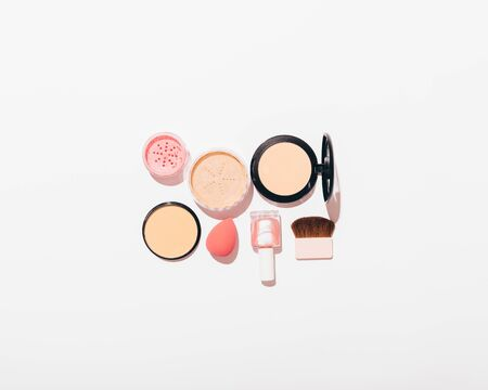 Set of womens cosmetic products on white background with copy space. Top view of blush, powder, brushes and nail polish.