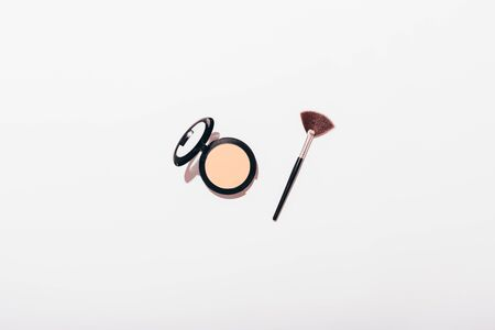 Compact powder and makeup brush on white background with copy space, minimal flat lay composition.