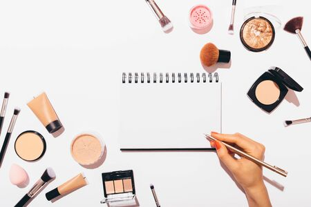 Female hand writing in empty notebook near makeup products on white background, top view. Flat lay composition of cosmetics and accessories.