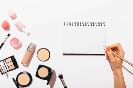 Females hand writing in blank blank notebook next to makeup products and accessories on white background, flat lay.