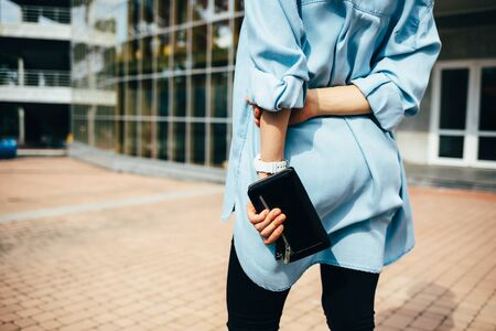 Rear view young woman wearing blue denim shirt is standing outside in city on summer day holding black small bag.