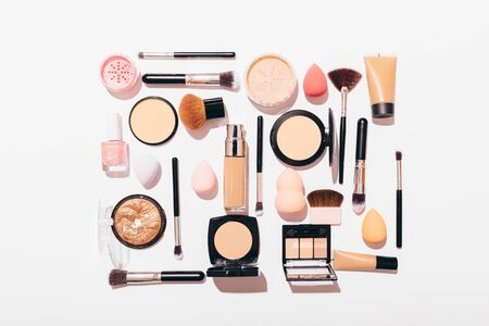 Flat lay composition set for professional makeup on white background. Top view of womens cosmetics and tools in frame.