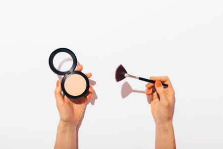 Female hands holding pressed powder and makeup brush on white background, flat lay concept composition with hard light.