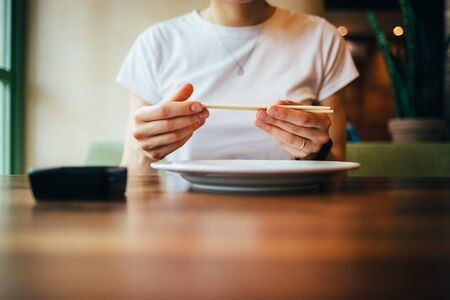 Close-up of female hands holding chopsticks. Young woman is preparing to eat sushi sitting at table in restaurant.