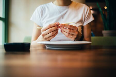 Young woman adjusts chopsticks placing in correct position between fingers while sitting at table in restaurant. Stock Photo - 129737797
