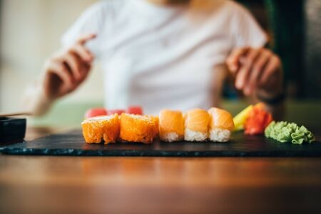 Close-up of served plate of sushi. Young woman sitting at table in restaurant is going to eat Japanese food.