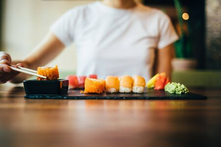 Young woman dipping roll in soy sauce. Female eating sushi sitting at table in restaurant.