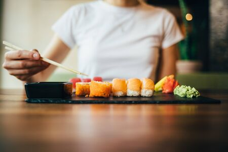 Womans hand holding chopsticks over plate with set of sashimi and sushi rolls. Unrecognizable young woman eating Japanese food sitting at table in restaurant.