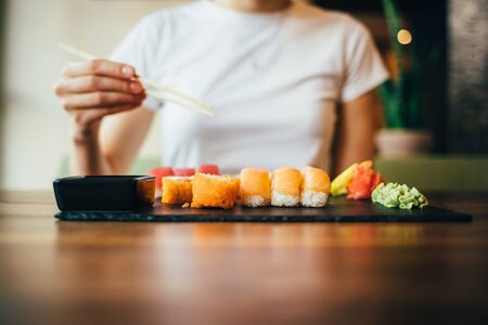 Unrecognizable young woman eating Japanese food sitting at table in restaurant. Females hand holding chopsticks over plate of sushi.