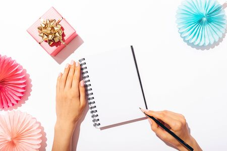 Womans hands writing in blank notepad near festive bright pink gift box with golden bow and paper party decorations on white background with copy space, view from above. Stockfoto