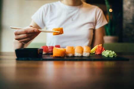 Young woman eating sushi sitting at table in restaurant, close-up. Female hand holding sushi with chopsticks over the plate.