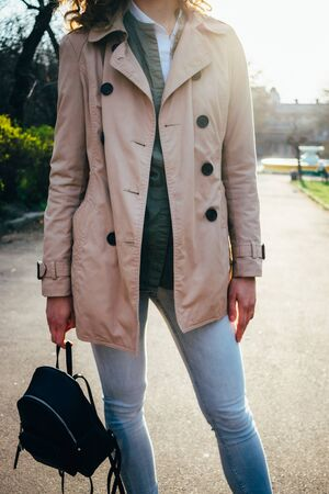 Unrecognizable stylish young woman dressed in beige coat with buttons holds backpack in her hand while standing outside, details of everyday clothes. Stock Photo