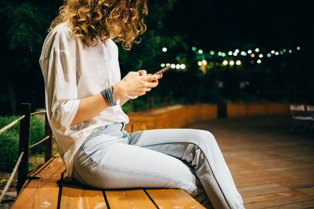 Close-up young woman wearing white shirt and blue jeans sitting on bench typing on smart phone on summer night in park with green trees and festive lights. Stock Photo