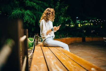 Unrecognizable young woman wearing white shirt and blue jeans sitting on bench typing on smart phone on summer night in park with green trees. Stock Photo