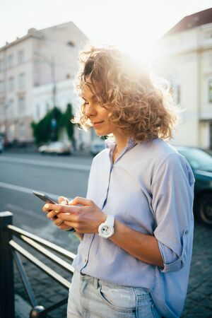 Happy young woman texting and smiling on smart phone standing near road with cars wearing blue shirt and jeans on summer day, sun flare from behind.
