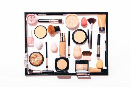 Top view of womens makeup products and tools in frame. Flat lay composition set for professional cosmetics on white background.