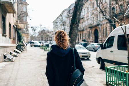Back view young woman with curly hair wearing black coat and backpack walking through city street next to road and cars on autumn day.