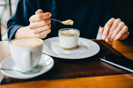 Close-up of a woman in a cafe eating a dessert