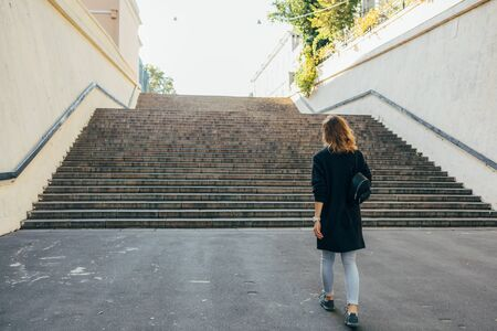 Woman with curly hair walks up the stairs in the city