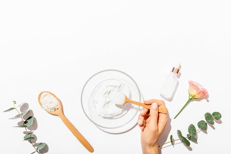 Womans hand holding spoon of cosmetic clay to make face mask next to bottle of serum and eucalyptus branches on white background with copy space, flat lay composition.