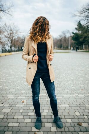 Woman with curly hair in a beige coat in a park, vertical image