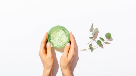 Females hands holding jar of clear aloe vera gel next to eucalyptus branches on white table, minimal flat lay composition.