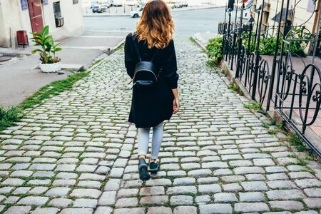 Young slender woman with curly hair walks in the old city Banco de Imagens