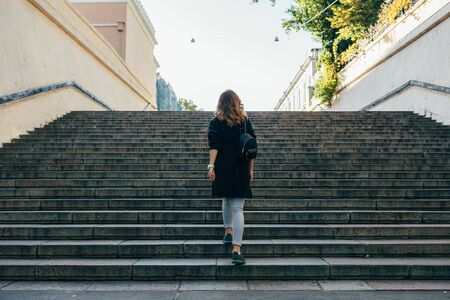 Woman with curly hair climbs the stairs in the city