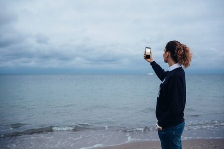 Woman with curly hair in jeans photographs the sea on a mobile phone Banco de Imagens