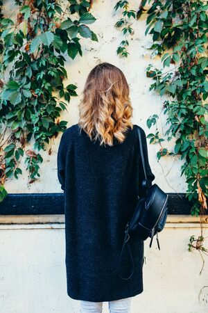 View from the back of a woman with curly hair in a sweater