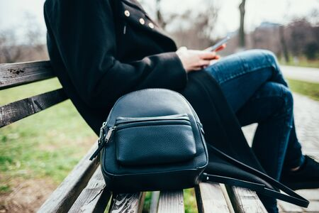 Close-up of a woman with a bag on a bench