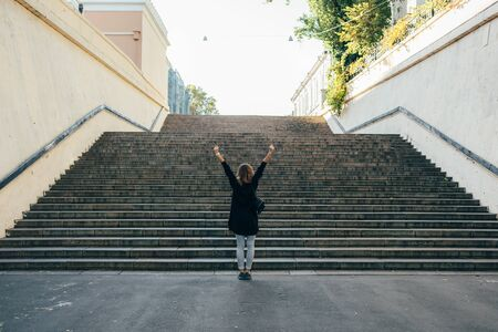 Woman with curly hair in a sweater stands near the city stairs