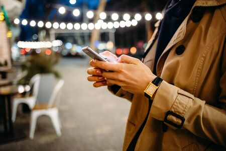 Woman in a beige coat with a phone in her hands on a night street