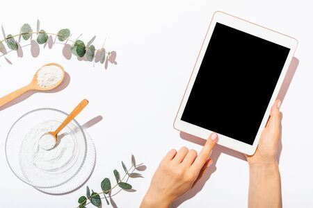 Womans hands using blank-screen tablet device next to homemade organic cosmetics clay mask on white table among eucalyptus twigs, top view.