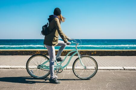 Woman riding a bicycle on the coast in cold weather Banco de Imagens