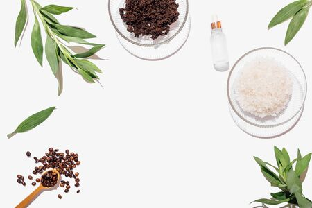 Homemade coffee scrub ingredients and fresh green leaves on white table with empty place in center, flat lay arrangement. Stock fotó