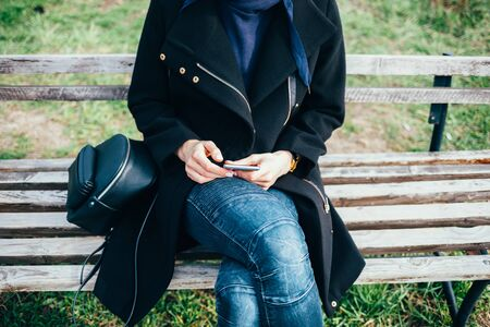 Woman in a black coat with a phone on a bench