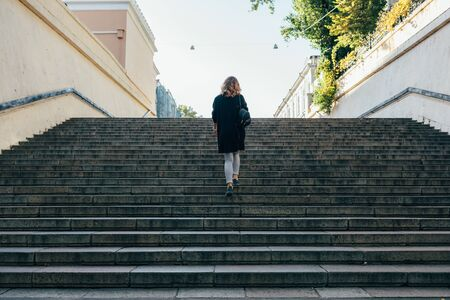 Woman with curly hair up the stairs in the city