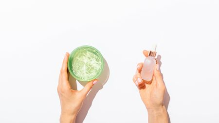 Womans hands holding natural cosmetics products jar with aloe gel and bottle of serum on white background with copy space, flat lay composition.