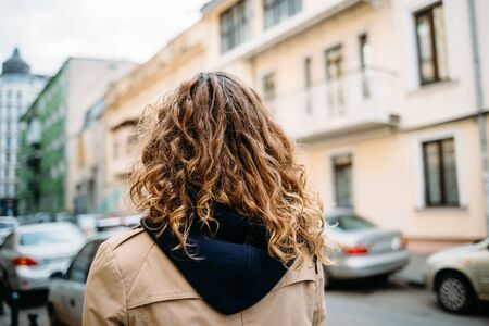 Woman with curly hair in a beige coat with a hood walks around the city, rear view