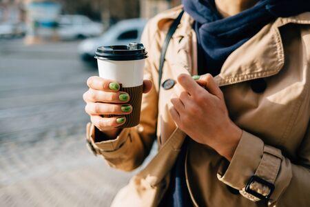 Woman in beige coat holding a cup of coffee in hands Banco de Imagens