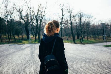 Young woman with curly hair in a black coat with a bag walks around the city